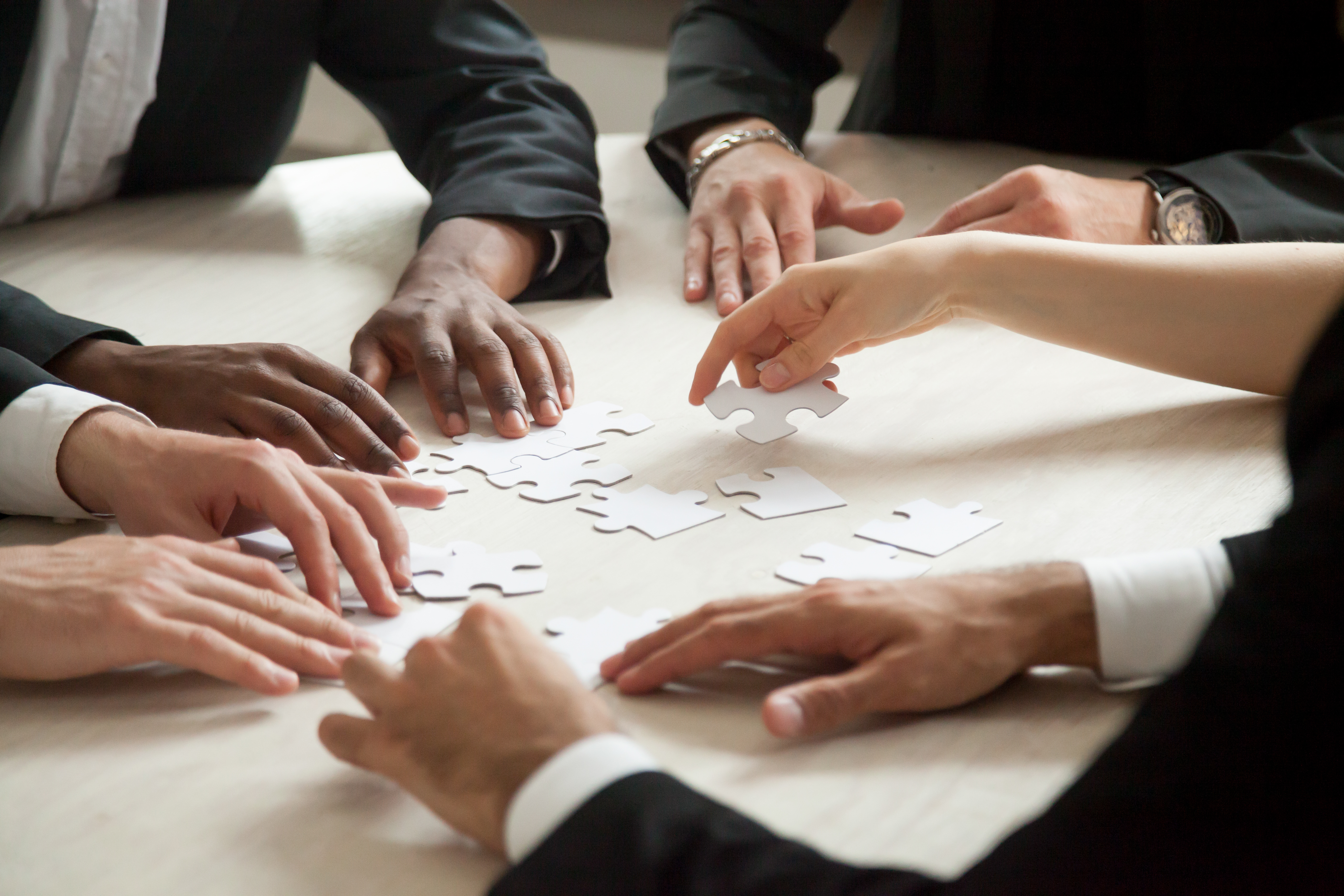 Close-up-of-multiethnic-team-solving-blank-puzzle-game