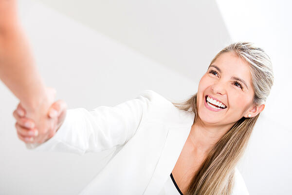 Business woman giving a handshake and looking happy