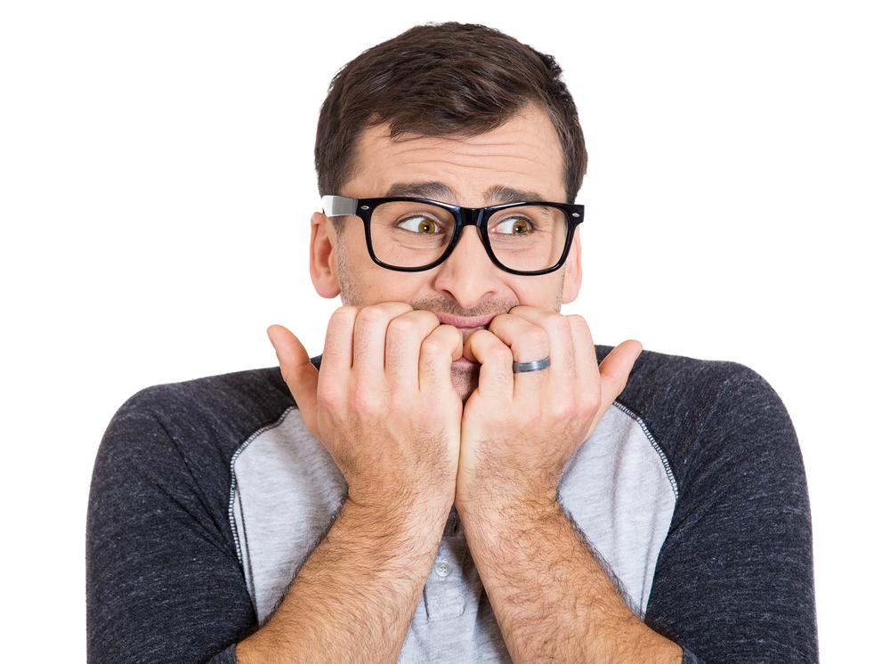 Closeup portrait of nervous, stressed young nerdy guy man with eyeglasses biting fingernails looking anxiously craving something isolated on white background. Negative emotion expression feeling