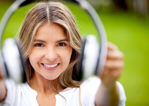 Woman portrait holding big headphones and smiling outdoors