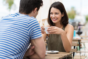 Young woman enjoying a cup of coffee outdoors at a street cafe as she sits chatting to her boyfriend or husband in the summer sun