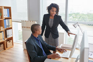 afro-american-woman-pointing-computer-screen-talking-junior-male-colleague