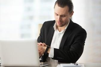 businessman-looking-wristwatch-work-desk-office