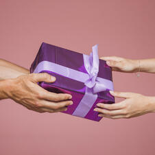close-up-two-hands-holding-purple-gift-boxes-against-colored-background