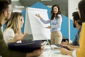 confident-young-team-leader-giving-presentation-group-young-colleagues-as-they-sit-grouped-by-flip-chart-office