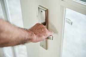 cropped-anonymous-man-holding-door-handle-open-door