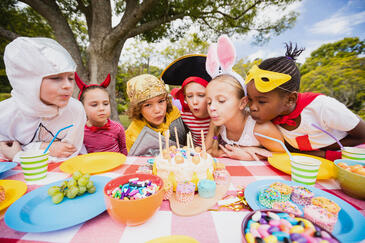 cute-children-blowing-together-candle-during-birthday-party