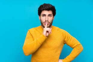 handsome-isolated-blue-wall-showing-sign-silence-gesture-putting-finger-mouth