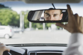 handsome-male-driver-adjusting-rearview-mirror-car