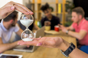 human-hand-holding-hourglass-front-people-background
