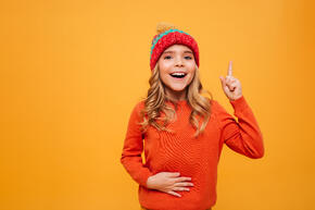 hungry-happy-young-girl-sweater-hat-holding-her-tummy-having-idea-while-looking-camera-orange