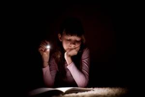 little-girl-is-reading-book-with-flashlight-dark-room-night