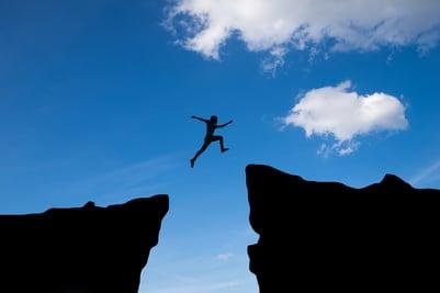 man-jump-through-gap-hill-man-jumping-cliff-sunset-background-business-concept-idea