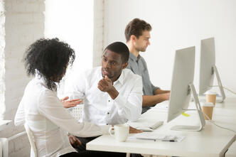 serious-african-american-colleagues-talking-discussing-project-together-workplace