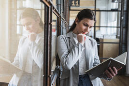 serious-young-woman-looking-diary-office