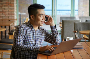 side-view-asian-guy-having-phone-call-while-working-laptop