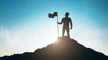 silhouette-man-with-flag-mountain-top-sky