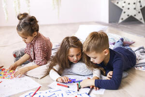 three-focused-children-are-playing-floor-drawing-coloring-books