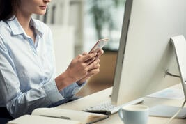 unrecognizable-woman-sitting-office-front-computer-using-smartphone