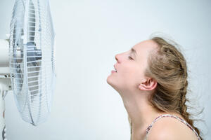 young-woman-sitting-fan-with-closed-eyes-from-pleasure-summer-heat