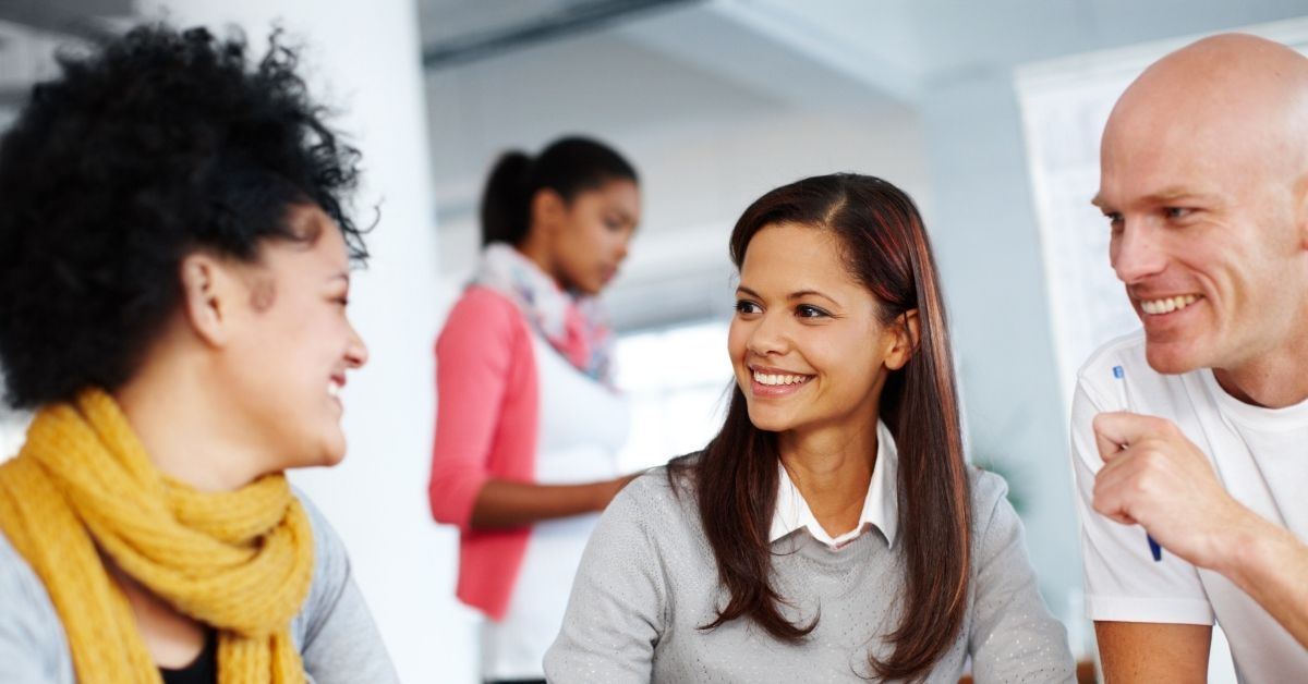 Group of coworkers smiling working on group project with woman in background left out