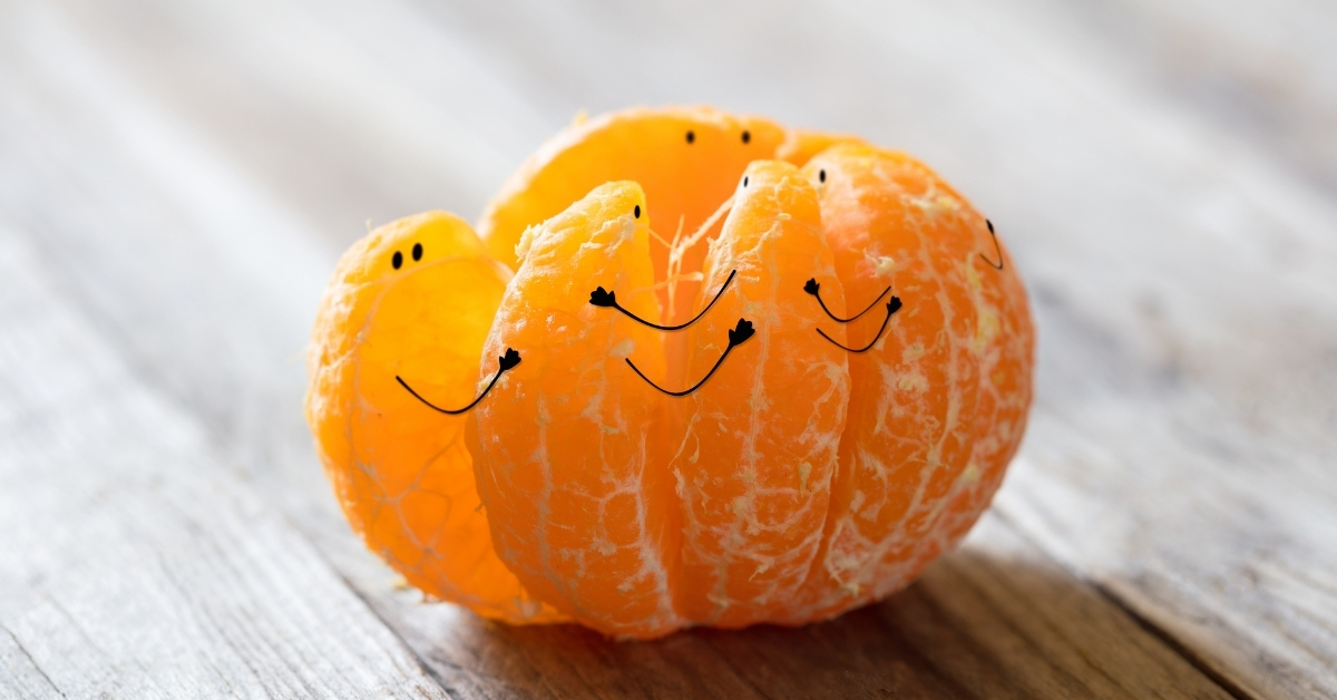 An orange starting to separate with eyes drawn on the pieces and arms connecting each section as if they were holding it together