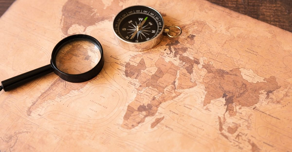 sepia map with magnifying glass and compass