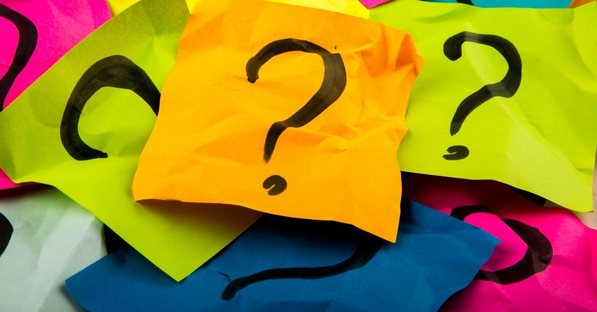 Bold, sharpie question marks on colorful, crumpled sticky notes piled on top of each other