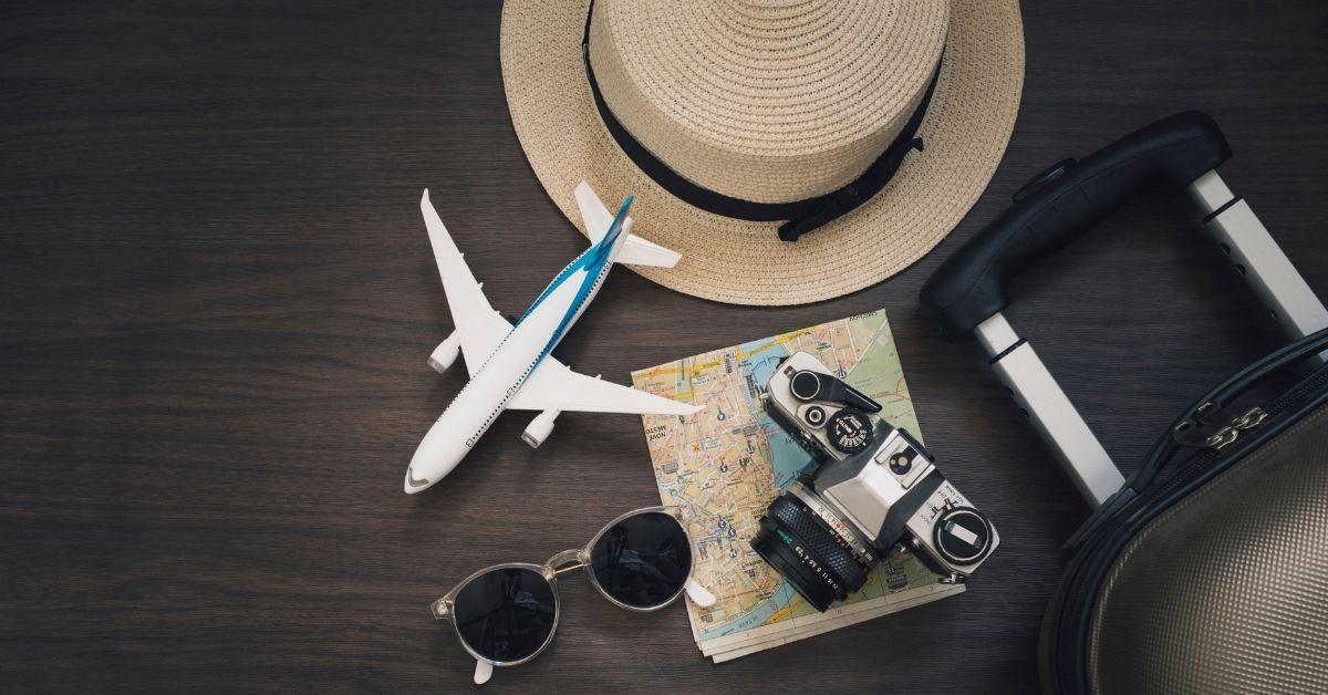 travel items: large hat, airplane, camera, sunglasses, map, suitcase handle on dark wood background
