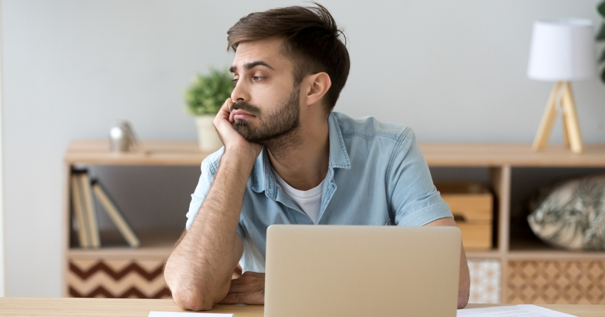 Man at computer staring off into space, distracted and unproductive