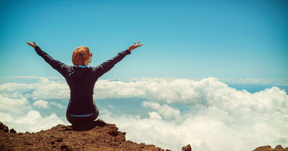 person sitting on a ledge at the top of a mountain looking out at the sky and clouds triumphant