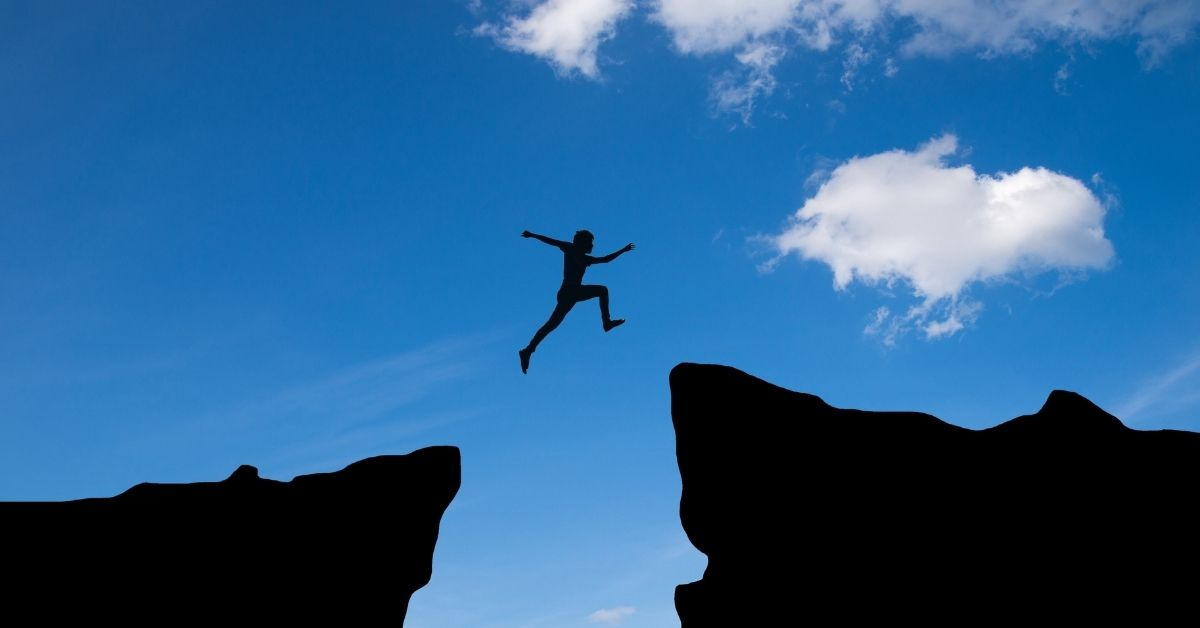 person jumping from one rock to another with a large gap in between on top of a bright blue slightly cloudy sky