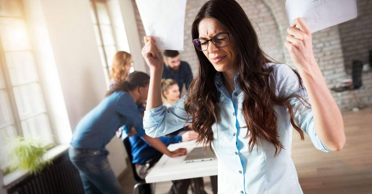 woman holding papers in the air frustrated or overwhelmed with group of coworkers in the background working