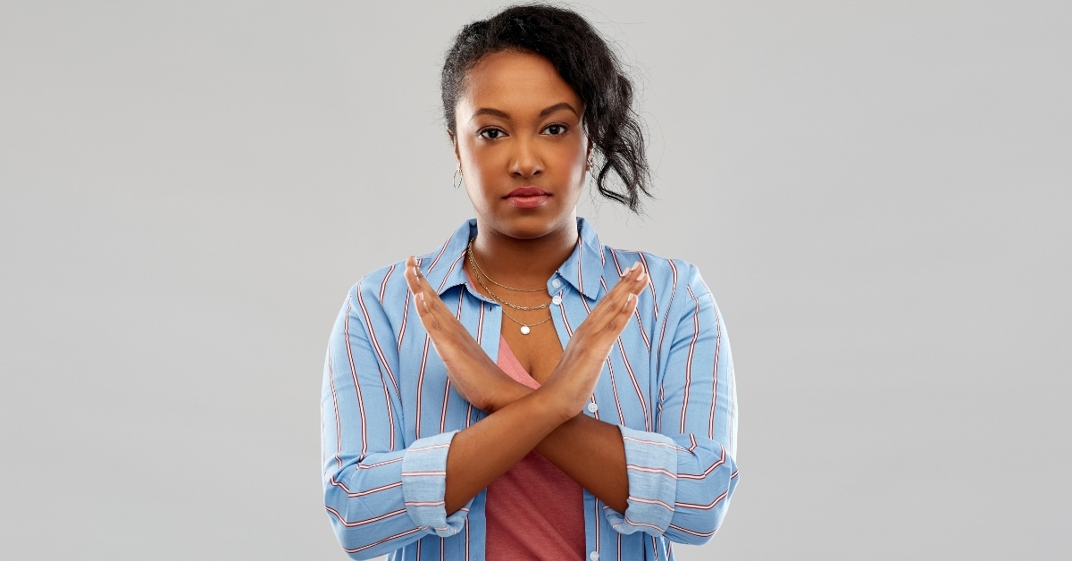 Woman of color crossing her arms in front of her chest to signify 'no'