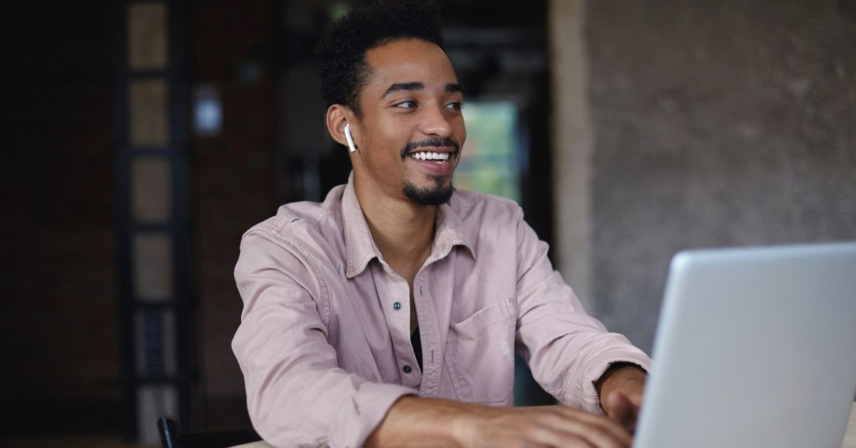 dark skinned man sitting at laptop with headphones on a virtual meeting